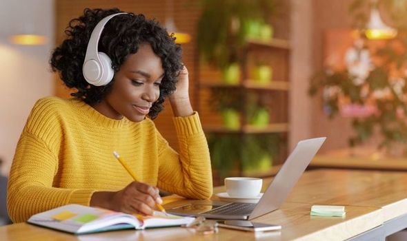 Woman works on laptop while wearing headphones